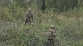 Two military standing in the field and talk with a gun in his hand.  stock footage