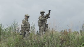 Two military standing in the field and talk with a gun in his hand.  stock video
