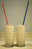 Two milkshakes on the background of blue wall. Two multi fruit, orange, kiwi milkshakes with blue and red drinking straws royalty free stock photos