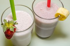 Two milkshakes with banana and strawberry stock photo