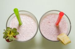 Two milkshakes with banana and strawberry. With straws from the top view stock photography