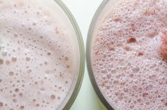 Two milkshakes with banana and strawberry royalty free stock images