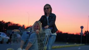 Two millennials girlfriends in street clothes have fun in a supermarket parking lot at sunset. Riding a shopping cart