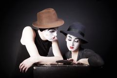 Two mimes in hats with a suitcase Royalty Free Stock Images
