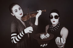 Two mimes playing a violin for the money Stock Images