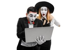 Two mimes saw something inappropriate. On a notebook screen. Male and female mime actors showing a pantomime scene. Shock content in internet stock image