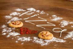 Two mini pizzas with sausage and cheese on wood table Royalty Free Stock Images