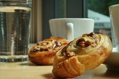 Two mini raisin bun dropped besided coffee cups and a glass of water royalty free stock photo