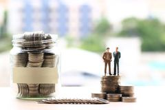 Two miniature businessman standing on coins money and glass bottle on city background, Investment and business concept stock images