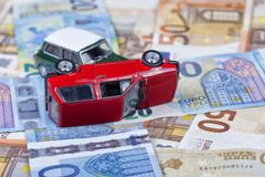 Two miniature cars simulate a traffic accident circulating above. Euro bills background Stock Photo