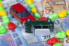 Two miniature cars simulate a traffic accident circulating above. Euro bills between streets marked with colored stones Stock Images