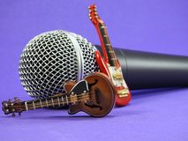 Two miniature electric guitars propped up on a dynamic microphone. Two miniature electric guitars propped up on a dynamic hand held vocal microphone. Purple royalty free stock images