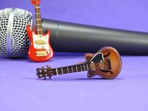 Two miniature electric guitars propped up on a dynamic microphone. Two miniature electric guitars propped up on a dynamic handheld vocal microphone. Purple stock images