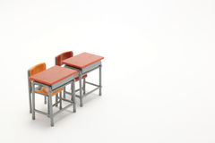 Two miniature school desks on white background. Classroom image royalty free stock images