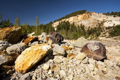 Two mining helmets in an open pit quarry. Two mining helmets in an open pit gold quarry Royalty Free Stock Images
