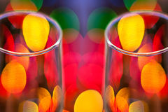 Cups of Cheer. Two mirror effect wine glasses with very shallow depth of field focus and Christmas lights blurred out in the background stock images