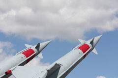On Guard for Peace. Two missiles tipped with red and peaceful blue sky Royalty Free Stock Photo