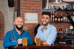 Two Mix Race Man In Bar Hold Glasses Sit At Counter, Drinking Beer, Cheerful Friends Meeting stock images