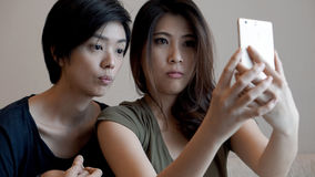 Two mixed race Asian girls taking selfie with smart phone Stock Photography