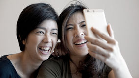 Two mixed race Asian girls taking selfie with smart phone Stock Photos