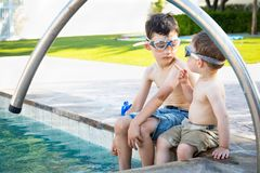 Two Mixed Race Chinese Caucasian Baby Points to Brother Wearing Swimming Goggles royalty free stock images