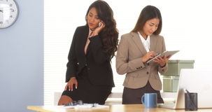 Two mixed race colleagues talking on mobilephone and using tablet Stock Images