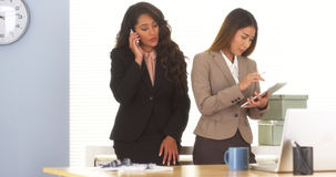 Two mixed race colleagues talking on smartphone and using tablet Royalty Free Stock Photo