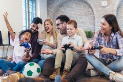 Two mixed race couple play video games with their children. Having fun Royalty Free Stock Photos