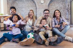 Two mixed race couple play video games with their children. Having fun Stock Photos