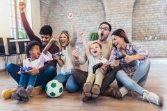 Two mixed race couple play video games with their children. Having fun Stock Images