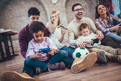 Two mixed race couple play video games with their children. Having fun Stock Photography