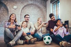 Two mixed race couple play video games with their children. Having fun Royalty Free Stock Photo