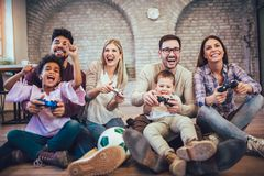 Two mixed race couple play video games with their children. Having fun Stock Photo