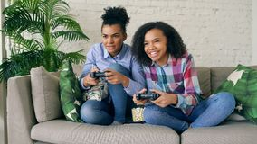 Two mixed race curly girls sitting on couch play console computer games with gamepad and have fun at home. Two mixed race curly girl friends sitting on couch Royalty Free Stock Photography