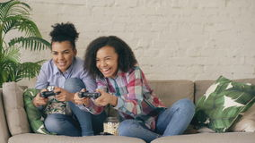 Two mixed race curly girl friends sitting on couch play console computer games with gamepad and have fun at home. Two mixed race curly girl friends sitting on stock video footage