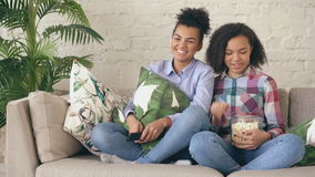 Two mixed race curly girl friends sitting on the couch and watch comedy movie and eat popcorn. Funny sisters relaxing. Together stock video footage