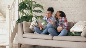 Two mixed race curly girl friends sitting on the couch and watch comedy movie and eat popcorn. Funny sisters relaxing. Together stock footage