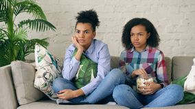Two mixed race curly girl friends sitting on the couch and watch thriller movie and eat popcorn at home. Two mixed race curly girl friends sitting on the couch Stock Photo
