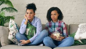 Two mixed race curly girl friends sitting on the couch and watch thriller movie and eat popcorn at home. Two mixed race curly girl friends sitting on the couch Royalty Free Stock Photography