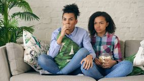 Two mixed race curly girl friends sitting on the couch and watch thriller movie and eat popcorn at home. Two mixed race curly girl friends sitting on the couch Royalty Free Stock Photo
