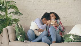 Two mixed race curly girl friends sitting on the couch and watch very scary movie on TV and eat popcorn at home stock footage