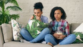 Two mixed race curly girl friends sitting on the couch and watch very scary movie on TV and eat popcorn at home. Two mixed race curly girl friends sitting on the Stock Image