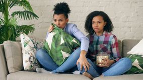 Two mixed race curly girl friends sitting on the couch and watch very scary movie on TV and eat popcorn at home. Two mixed race curly girl friends sitting on the Royalty Free Stock Images