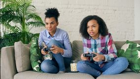 Two mixed race curly girls sitting on couch play console computer games with gamepad and have fun at home. Two mixed race curly girl friends sitting on couch Royalty Free Stock Image