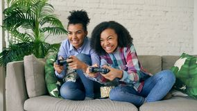 Two mixed race curly girls sitting on couch play console computer games with gamepad and have fun at home. Two mixed race curly girl friends sitting on couch Royalty Free Stock Photo