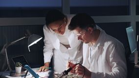 Two mixed race electronics engineers working with multimeter tester and other electronic devices. Man is in protective glasses stock video footage