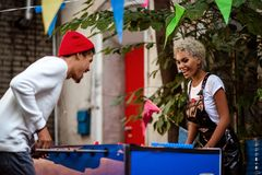 Two mixed race female and male friends play table football outdoor, entertain themselves. Positive stylish mulatto. People play outdoor game together. People Stock Photo