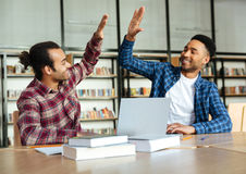 Two mixed race male students giving high five Royalty Free Stock Photo