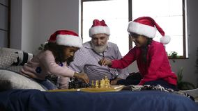 Two mixed race sisters playing chess on xmas eve. Two adorable african american sisters in santa hats playing chess on bed during family spending christmas time stock video
