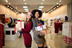 Two mixed race women with gift boxes in hands at store. Multi ethnic girls smiling with presents on christmas new year stock image